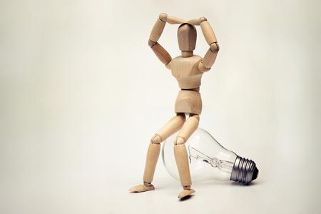 marioneta de madera: Wood Figure Mannequin sitting on an incandescent light bulb  Being stupid  Having no idea