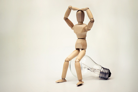 Wood Figure Mannequin sitting on an incandescent light bulb  Being stupid  Having no idea