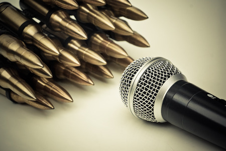 Microphone vs. Bullets / Freedom of the press is at risk concept / World press freedom day concept Archivio Fotografico