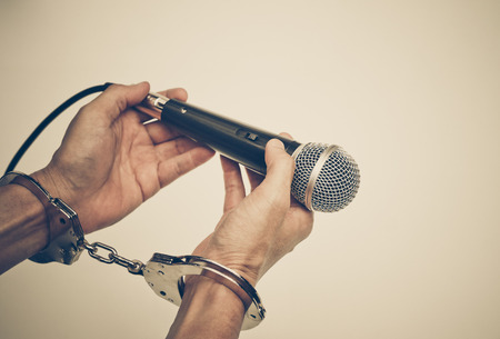 Hand holding a microphone with handcuffs  Freedom of the press is at risk concept - World press freedom day concept Stock Photo