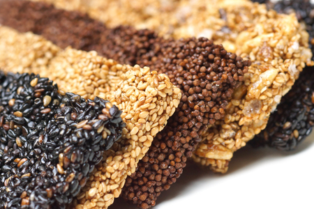 Closeup shot of different types of sesame bars in white, red, black colors  Healthy snack food concept Stock Photo