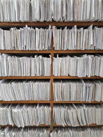 A cupboard full of paper files  inefficiency of paper based filing system Stock Photo
