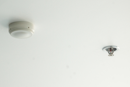 Fire detector and extinguisher with gray ceiling as background