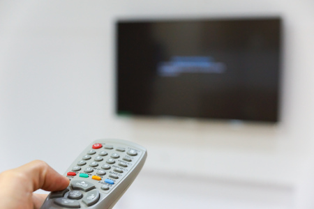 Hand holding a television remote trying to switch it on