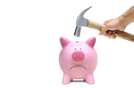 A sad pink piggy bank is about to be hit by a hammer Stock Photo