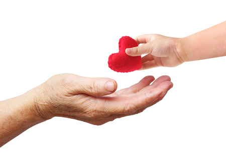 A young hand of a baby giving a red heart to an old hand of the elderly isolated with copy space to add text                       Stok Fotoğraf