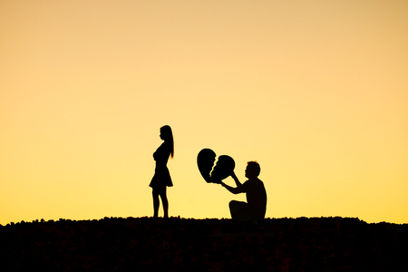 Man begging a woman for love by giving a big broken heart in sunset silhouette background / Disappointed love concept Stock Photo