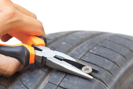 Removing a bolt from a flat tire using pliers