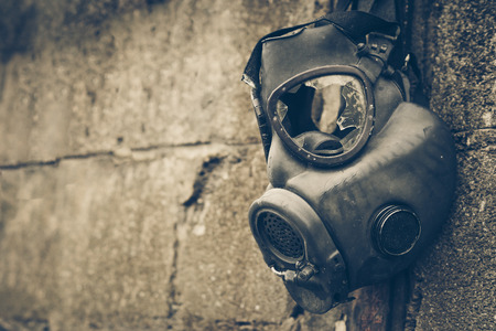Broken gas mask hung on the wall / Toxic chemical weapon concept