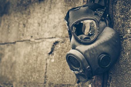 Masque à gaz cassé accroché au mur / concept d'arme chimique toxique Banque d'images