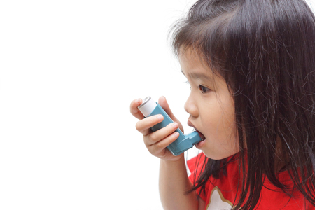 Una niña que usa un aerosol de tratamiento para tratar el asma y los problemas respiratorios aislados Foto de archivo