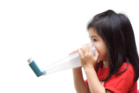 A girl using a treatment spray to deal with asthma and breathing problems isolated Stockfoto