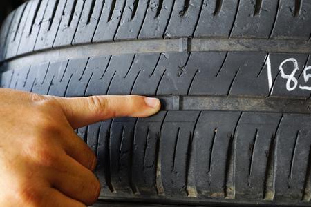 Dito puntato sull'indicatore di usura del battistrada del pneumatico / Controllo e sostituzione del pneumatico per il concetto di sicurezza