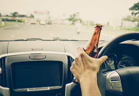 A driver holding alcoholic bottle while driving  Drunk driving concept