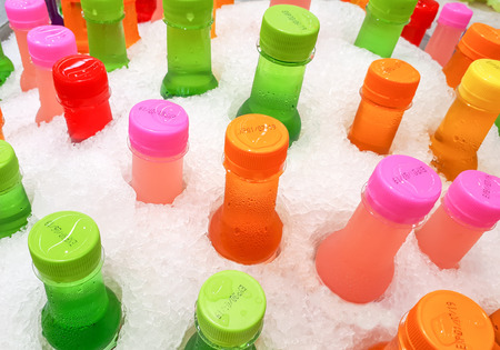 Colorful bottles of cool soft drinks in ice