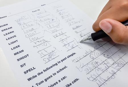 Student with a bad handwriting writing irregular verbs Archivio Fotografico