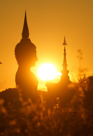 sunset in front of a buddhist sculpture