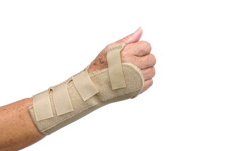 Old female hand wearing hand wrist therapy support glove isolated on white Imagens
