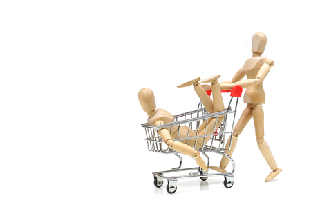 A wood figure Mannequin pushing a shopping card with another one inside / Labor market concept