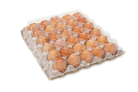 Chicken eggs in a tray with transparent plastic cover isolated on white background
