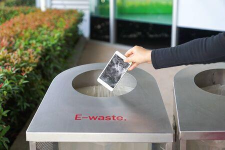 Hand, die ein altes, beschädigtes Smartphone in einen Mülleimer für Elektroschrott fallen lässt