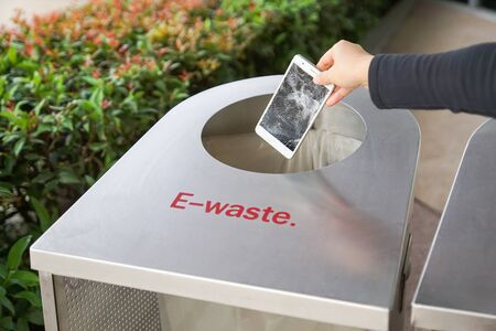 Hand dropping an old, damaged smartphone into a bin for e-waste garbage Standard-Bild - 126832420