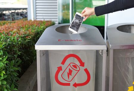 Hand dropping a smartphone into a bin for e-waste