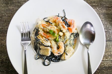 Top view of black spaghetti with shrimps and squid on a white dish Standard-Bild - 126832430