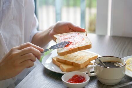 Having breakfast - Hand spreading strawberry jam on toast with coffee on table Standard-Bild - 127285026