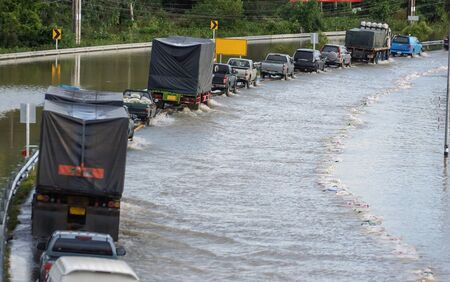 Car, trucks, and lorries running through the flooded road Stock Photo