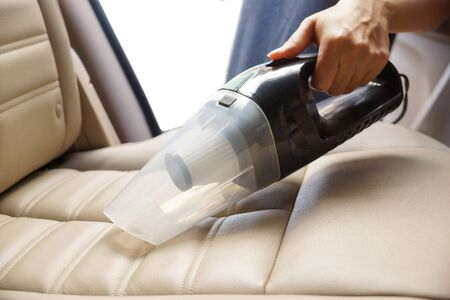 Cleaning a car using a vacuum cleaner Stockfoto