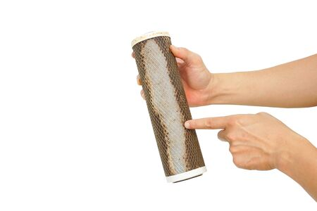 Hand holding dirty water filter cartridge on white isolated background