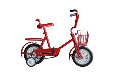 An old style bicycle for kid in red color with training wheels on isolated background