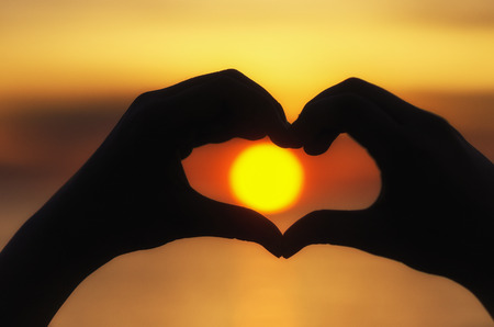 sweethearts: Silhouette of hands in form of heart when sweethearts have touched Stock Photo