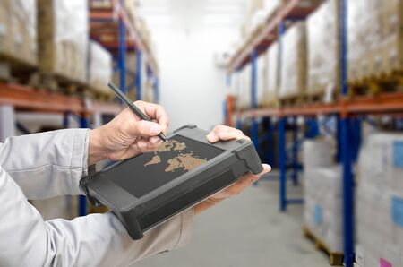 Smart factory - Rugged computers tablet and Bluetooth barcode scanner in front of modern warehouse in factory use for logistics. Stock Photo