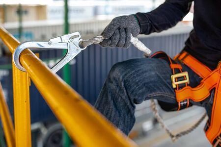 Bauarbeiter mit Sicherheitsgurt und Sicherheitsleine, die am Bau arbeiten Standard-Bild