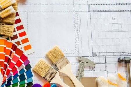 Professional decorator drawing on a house project with work tools. Фото со стока