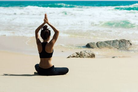 Young healthy woman practicing yoga on the beach at sunset Фото со стока
