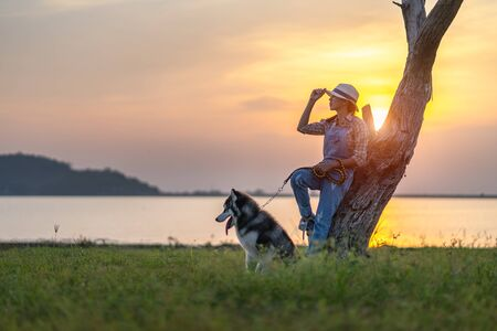A beautiful girl is sitting on the lawn with her dog. Siberian husky dog with blue eyes. Bright green trees and grass are in the background. Friendship between man and animals