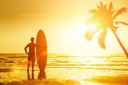 Happy surfer  standing with surfboards on the beach