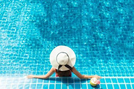 Asia woman relaxing on donut lilo in the pool water in hot sunny day. Summer holiday idyllic Фото со стока