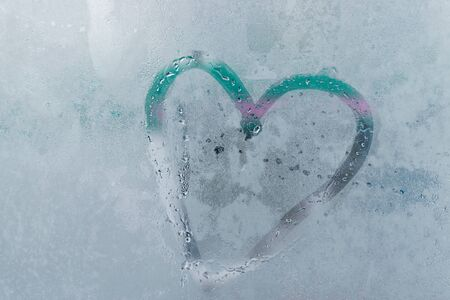 drawing heart on misted or frozen glass, love heart sunny natural background. Valentine day emotion