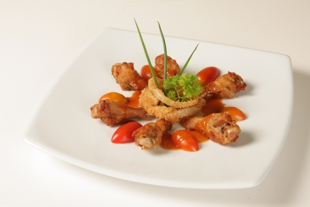 Thai fried chicken topped with tomato sauce on a white background Stock Photo