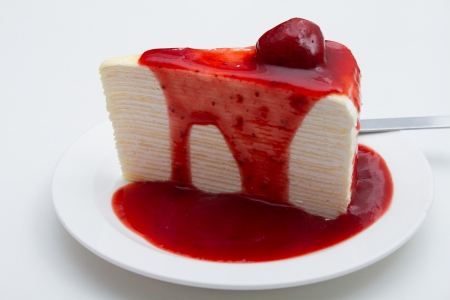 Crepe cake, strawberry sauce on a white background