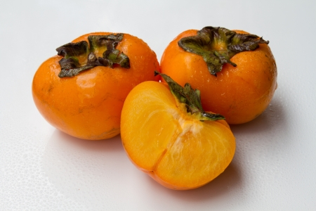 Half persimmon on a white background