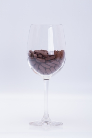 Vitamins in a glass of wine  on a white background photo