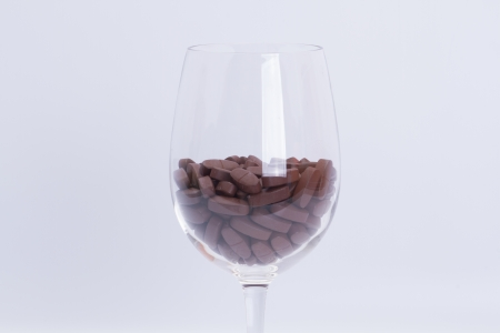 Vitamins in a glass of wine on a white background