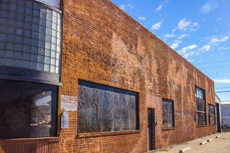 Side of Abandoned Brick Building With Curved Glass Stock Photo