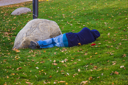 Man Sleeping In Park In Fall Stock Photo