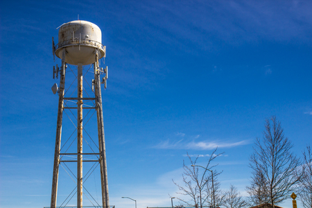 Rusted Water Tank Against Blue Sky Background